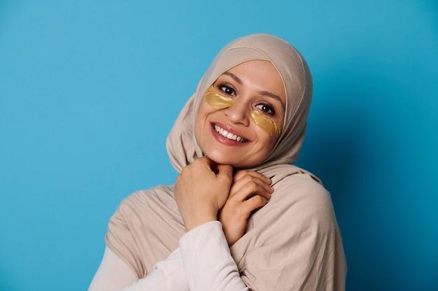 Piękna kobieta z zakrytą głową w hidżabie, uśmiechając się do kamery z hydrożelowymi łatami kolagenowymi pod oczami. odosobniony