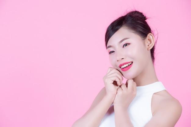 Piękna kobieta z zdrową skórą i pięknem na różowym tle.