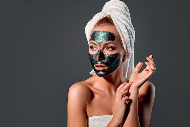 Piękna kobieta z zieloną maską peel-off na szarej ścianie.