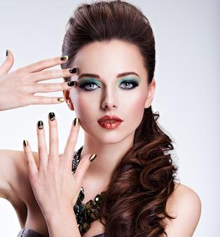 Piękna kobieta z zielonym makijażem i kreatywnym kolorem paznokci