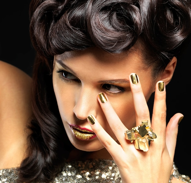 Piękna kobieta z złote paznokcie i makijaż moda oczu. brunet dziewczyna model z stylowym manicure na czarnej ścianie