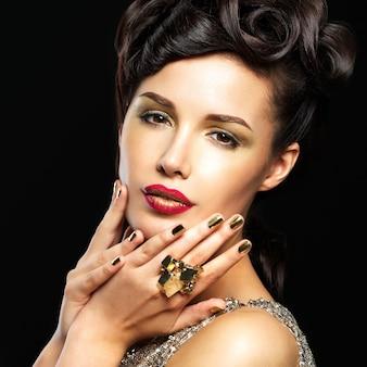Piękna kobieta z złote paznokcie i makijaż moda oczu. brunet dziewczyna model z stylowym manicure na czarnym tle