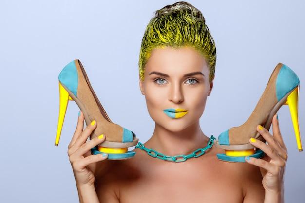 Piękna kobieta z żółtymi trzyma kolorowymi butami
