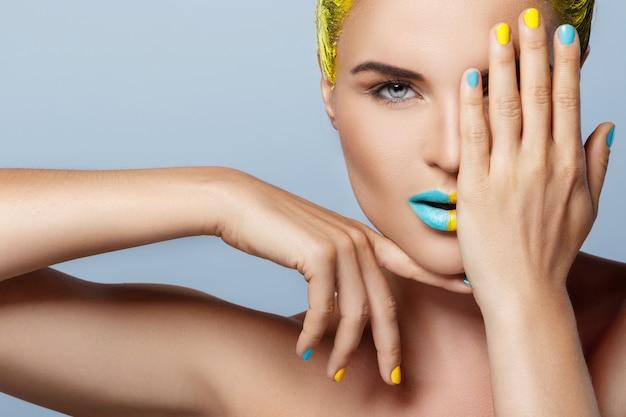 Piękna kobieta z żółtymi włosami i kolorowymi paznokciami i ustami