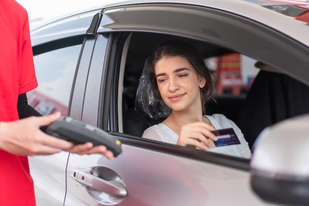 Piękna kobieta za pomocą karty kredytowej z terminalem do płatności kartą, aby zapłacić za tankowanie benzyny na stacji benzynowej