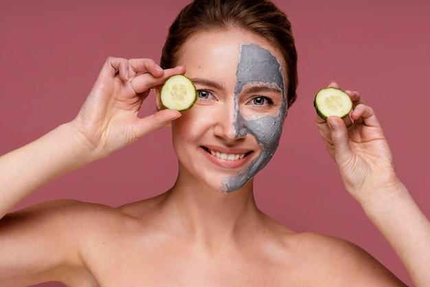 Piękna kobieta za pomocą plasterków ogórka do oczu