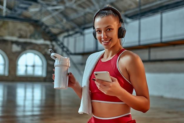 Piękna kobieta za pomocą smartfona i słuchanie muzyki w słuchawkach pije shake proteinowy podczas ćwiczeń w sali fitness. koncepcja sportu i technologii. styl życia i zdrowie.