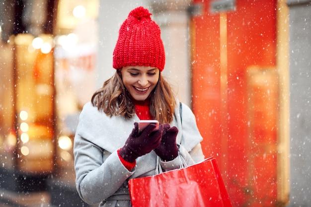 Piękna kobieta za pomocą telefonu komórkowego podczas zakupów w okresie zimowym