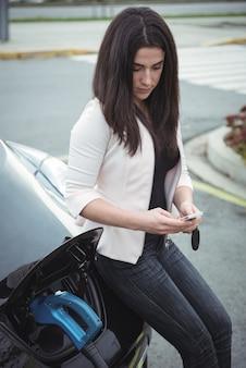 Piękna kobieta za pomocą telefonu komórkowego pone podczas ładowania samochodu elektrycznego