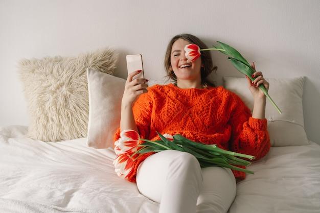 Piękna kobieta za pomocą telefonu w łóżku w domu. kobieta raduje się z tulipanów
