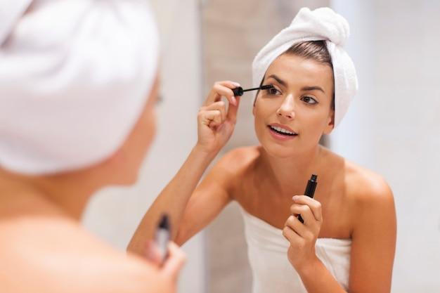 Piękna kobieta za pomocą tuszu do rzęs w łazience