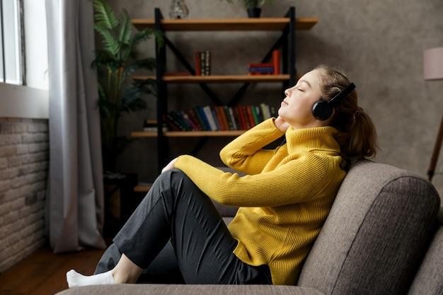 Piękna kobieta zadowolony, słuchanie muzyki w słuchawkach, siedząc na kanapie w domu