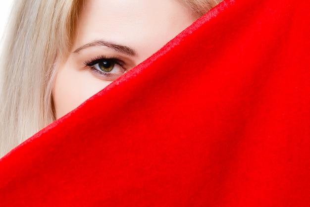 Piękna kobieta zakrywa twarz czerwonym suknem.
