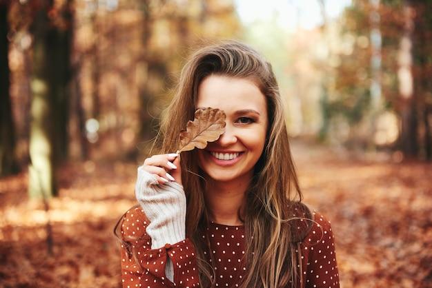 Piękna kobieta zakrywająca oko jesiennymi liśćmi