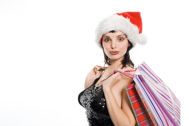 Piękna kobieta zakupów świątecznych z prezentem w czerwonej czapce
