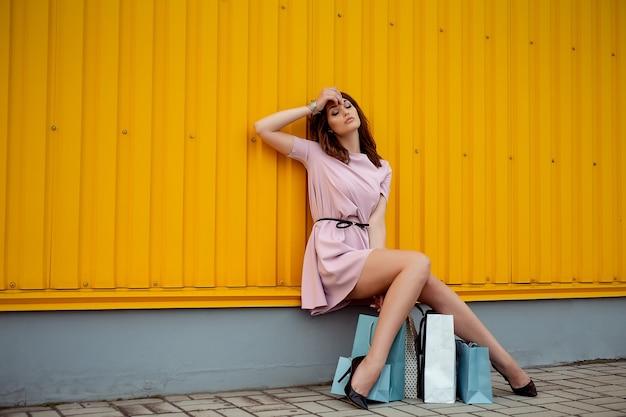 Piękna kobieta zakupy z zewnątrz torby papierowe