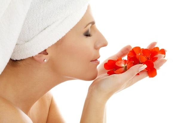 Piękna kobieta zapachu płatków czerwonych kwiatów