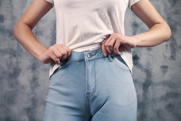 Piękna kobieta zapina niebieskie dżinsy