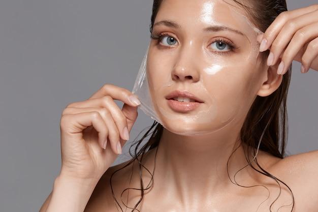 Piękna kobieta zdejmując maskę peeling z twarzy i patrząc w kamerę