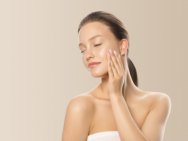 Piękna kobieta zdrowa skóra koncepcja pielęgnacji portret z rąk z bliska beżowym tle. zdjęcia studyjne