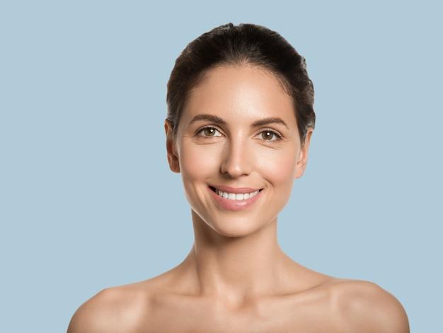 Piękna kobieta zdrowa skóra uroda twarz kosmetyczna koncepcja kolor tła. niebieski.
