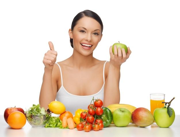 Piękna kobieta ze zdrową żywnością pokazująca kciuk w górę