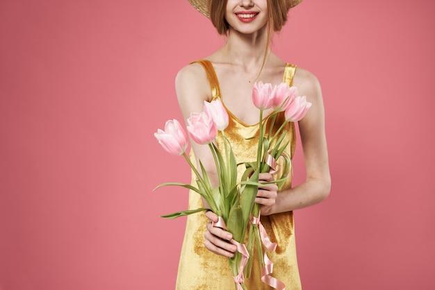 Piękna kobieta złota sukienka i bukiet kwiatów wakacje elegancki styl różowy