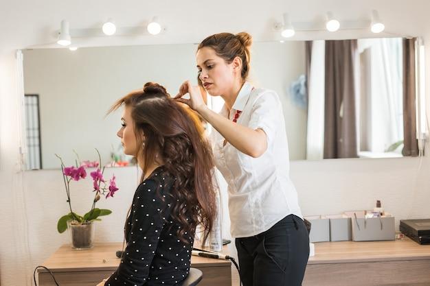 Piękna kobieta zostaje strzyżona przez fryzjera w salonie kosmetycznym