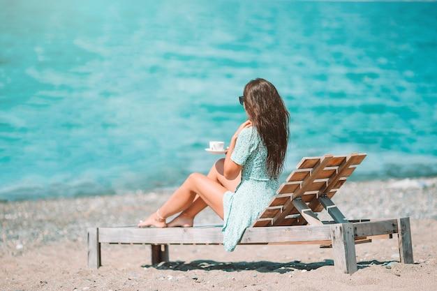 Piękna kobieta zrelaksować się na plaży przy filiżance kawy
