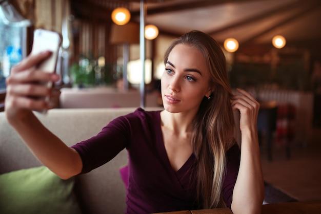 Piękna kobieta zrobić selfie w restauracji.