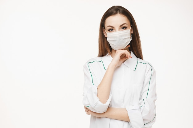 Piękna kobiety lekarka, pielęgniarka jest ubranym ochronną maskę lub medyczny sukni pozować lub. młoda kobieta w mundurze medycznych. pojęcie opieki zdrowotnej
