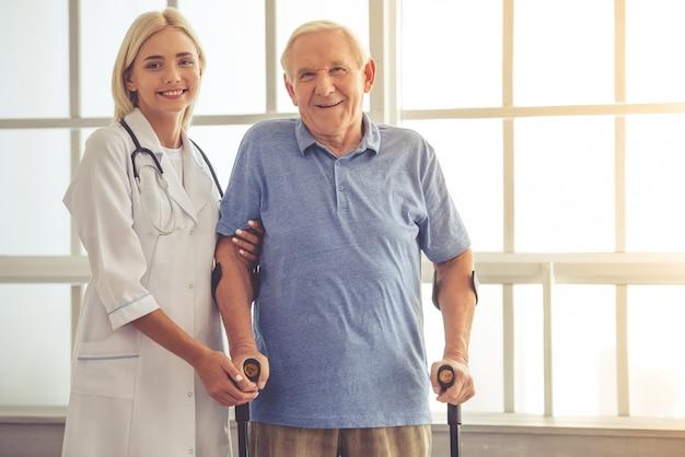 Piękna kobiety lekarka pomaga przystojnego starego człowieka.