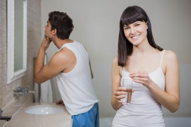 Piękna kobiety mienia pigułka, szkło woda i mężczyzna patrzeje w lustrze