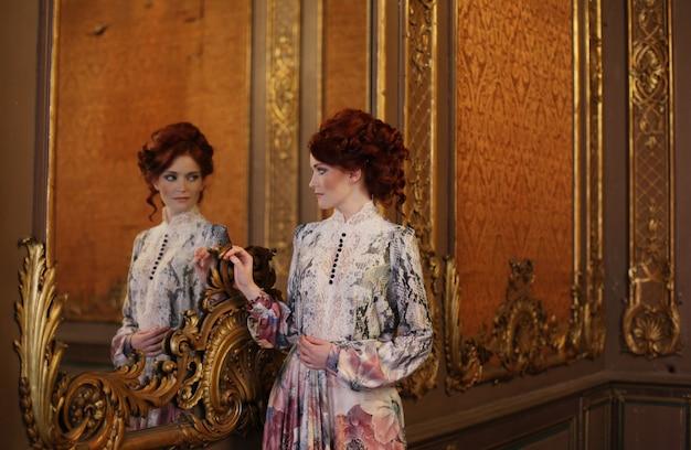 Piękna kobiety pozycja w pałac pokoju z lustrem.