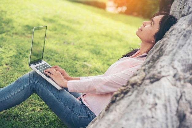 Piękna kobiety pracującej praca plenerowa używa laptop i smartphone pracujący w parku out.