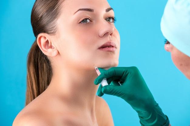 Piękna kobiety twarz i kosmetyczka ręki z strzykawką. lekarz wykonuje zastrzyk kosmetyczny. koncepcja czystego piękna