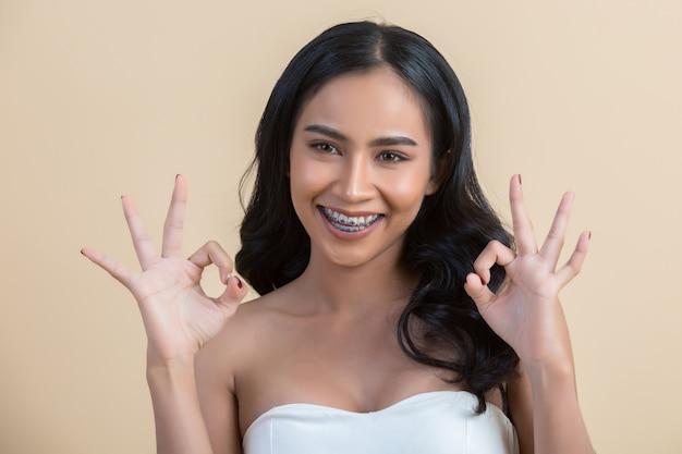 Piękna kobiety twarz robi ok znakowi