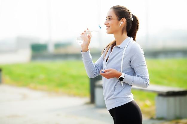 Piękna kobiety woda pitna i słucha muzyka po biegać