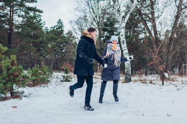 Piękna kochająca para biega w zima lesie wpólnie. ludzie bawią się na zewnątrz