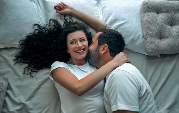 Piękna kochająca para całuje się w łóżku
