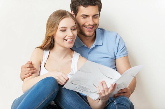 Piękna kochająca para. piękna młoda kochająca para siedzi na podłodze i razem czyta broszurę