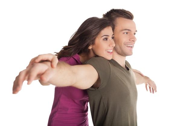 Piękna kochająca para. wesoła młoda kochająca para przytulająca się i uśmiechająca się do kamery stojąc na białym tle