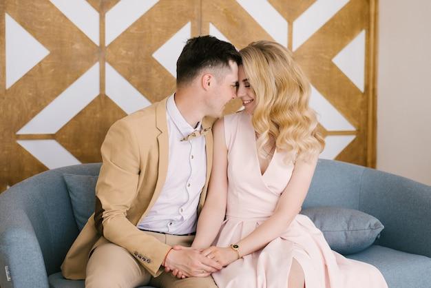 Piękna kochająca się młoda para w domu w pięknym wnętrzu i eleganckich strojach