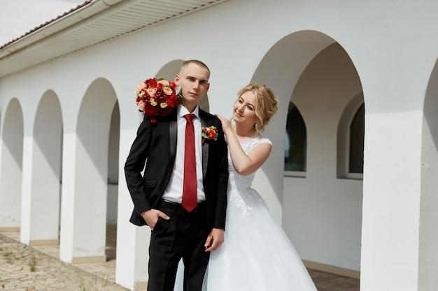 Piękna kochająca się para ślubna rejestruje małżeństwo i idzie wzdłuż pięknej promenady