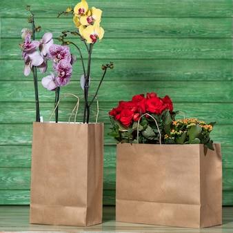 Piękna kolorowa orchidea, begonia, gardenia w torbie na zakupy z zieloną przestrzenią