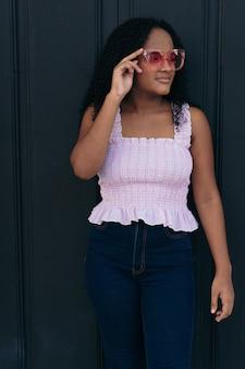 Piękna kolumbijska nastolatka stojąca przed starymi drzwiami