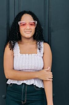 Piękna kolumbijska nastolatka z okularami przeciwsłonecznymi stojąca przed drewnianymi drzwiami.