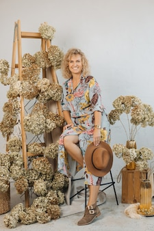 Piękna kompozycja kwiatowa z pięknymi suszonymi kwiatami hortensji, w stylowej przestrzeni, na drewnianych schodach. wśród nich jest szczęśliwa kobieta kwiaciarni w sukience