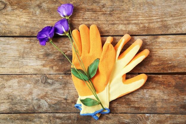 Piękna kompozycja kwiatowych i ogrodowych rękawiczek na drewnianym tle