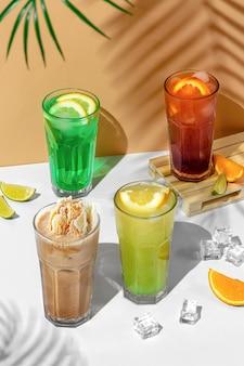 Piękna kompozycja martwa natura z czterema przezroczystymi szklankami letniego napoju. zielona lemoniada z limonką, miętą, cytryną i cytrusami na tropikalnym tle z cieniami palmy